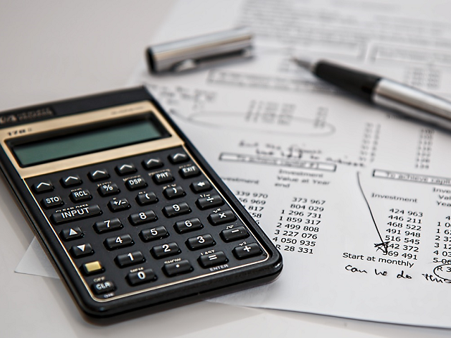 Calculator with open pen on investment papers.