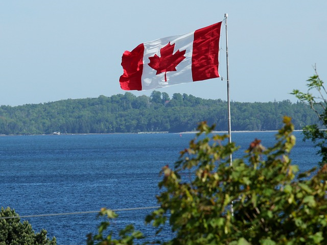 Canadian flag above lake and mountain view