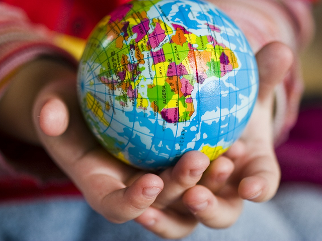 Child's hands holding earth globe.