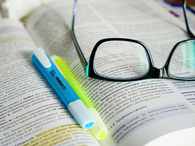 Glasses and highlighters on text book.