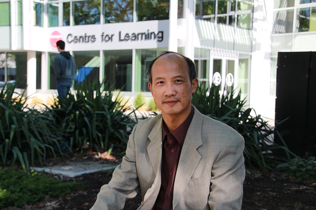 Norman Luo sitting outside OC's Student Services building.